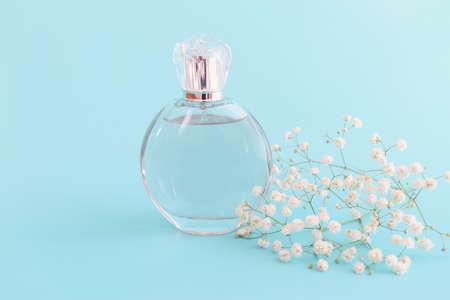 Image of elegant perfume bottle over blue pastel background