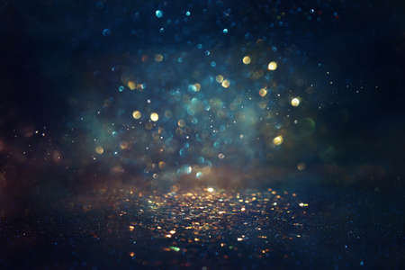 background of abstract glitter lights. gold, blue and black. de focused