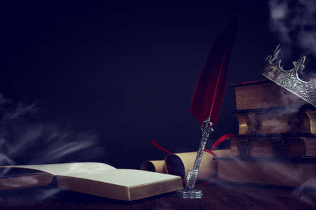 low key image of beautiful queen/king crown over old book and feather quill ink pen over wooden table. fantasy medieval period