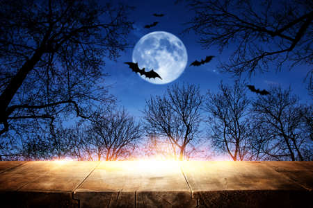 Halloween Holiday concept. Empty rustic table in front of scary and misty night sky, forest and full moon background. Ready for product display montage Standard-Bild