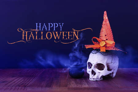 holidays halloween concept image. Pumpkin, witcher cauldron and skull over wooden table and black background