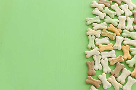 Top view of dog treats over green wooden background Standard-Bild