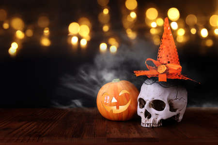 holidays halloween concept image. Pumpkin and skull over wooden table and black background