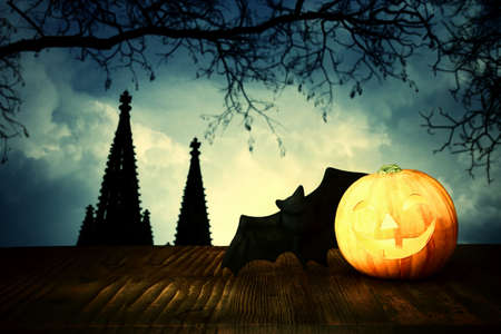 holidays halloween concept image. Pumpkin over wooden table and scarry night castle background