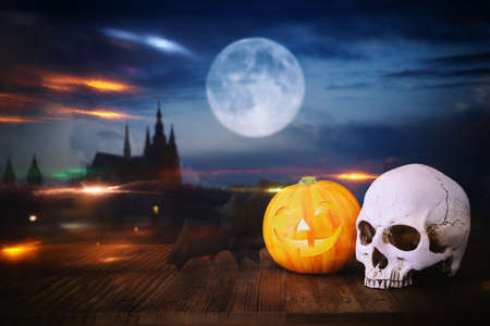 holidays halloween concept image. Pumpkin and skull over wooden table and scarry night castle background