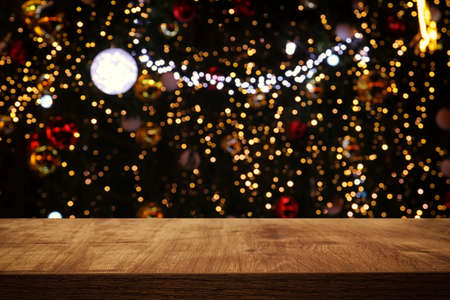Empty table in front of christmas tree with decorations background. For product display montage Standard-Bild