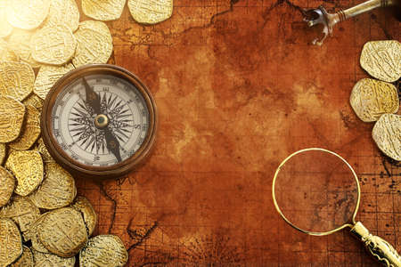 Old compass and gold coins treasure over antique map. top view Banque d'images
