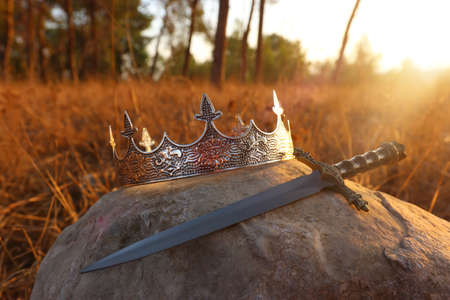 mysterious and magical photo of silver king crown and sword in the England woods over stone. Medieval period concept. 写真素材