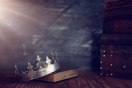 low key image of beautiful queen/king crown on old book. vintage filtered. fantasy medieval period 写真素材