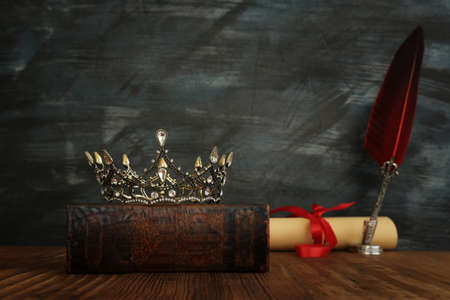 low key image of beautiful queen/king crown on the old books and feather quill ink pen over wooden table. fantasy medieval period