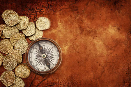 Old compass and gold coins treasure over antique map. top view