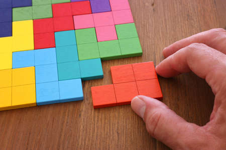 man's hand holding a square tangram puzzle, over wooden table