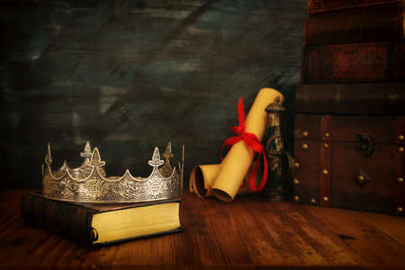 low key image of beautiful queen/king crown, old books and feather quill ink pen over wooden table. fantasy medieval period