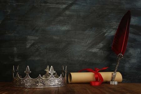 low key image of beautiful queen/king crown and feather quill ink pen over wooden table. fantasy medieval period 写真素材
