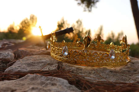mysterious and magical photo of gold king crown and sword in the England woods over stone. Medieval period concept.