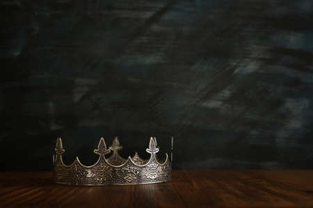 low key image of beautiful queen/king crown over wooden table. vintage filtered. fantasy medieval period 写真素材
