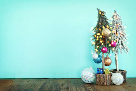 Image of christmas tree with decorations in front of pastel blue background
