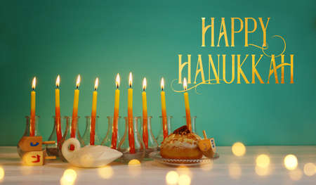 Image of jewish holiday Hanukkah with creative menorah (traditional Candelabra), donut and wooden dreidel (spinning top)