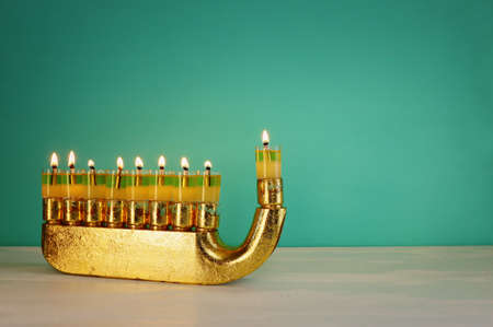 Religion image of jewish holiday Hanukkah background with gold menorah (traditional candelabra) and candles