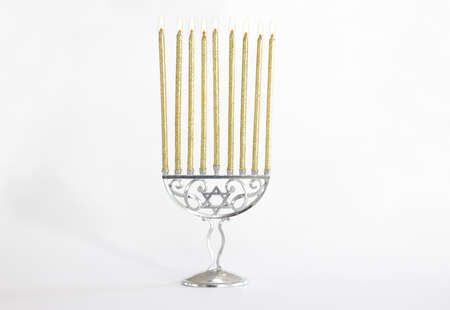 religion image of jewish holiday Hanukkah with white menorah (traditional candelabra) and gold candles isolated over white background