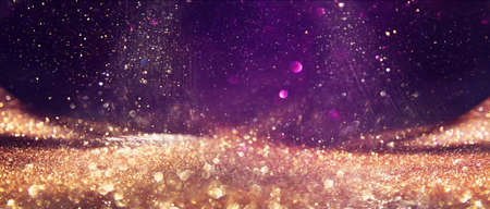 background of abstract glitter lights. Gold ,purple and black. de focused
