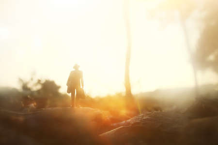 Surreal image of mysterious man walking alone during sunset