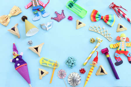 Purim celebration concept (jewish carnival holiday) over wooden blue background. Top view, flat lay
