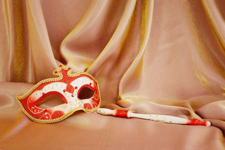 Photo of elegant and delicate Venetian mask over gold silk background