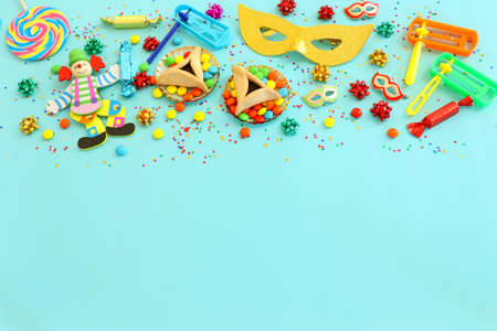 Purim celebration concept (jewish carnival holiday) over blue background. Top view, flat lay