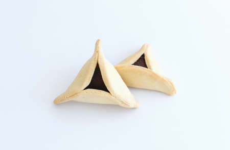 Purim celebration concept (jewish carnival holiday). Traditional cookie isolated on white