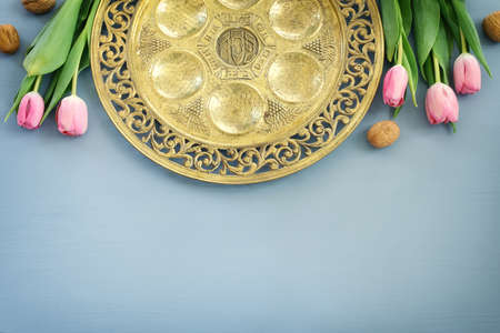 Pesah celebration concept (jewish Passover holiday). Traditional pesah plate text in hebrew: Passover, horseradish, celery, egg, bone, maror, sweet dates jam
