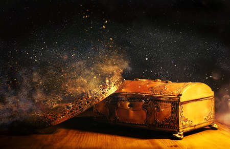low key image of beautiful queen/king crown over gold treasure chest. vintage filtered. fantasy medieval period Stockfoto