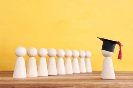 Image of education concept. Wooden people figure with graduation hat