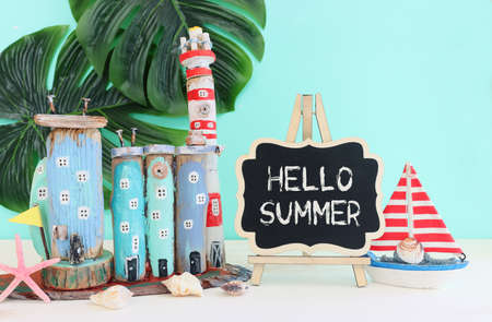 Nautical concept with sea life style objects as boat, driftwood beach houses, seashells and starfish over wooden table and blue background Stock Photo