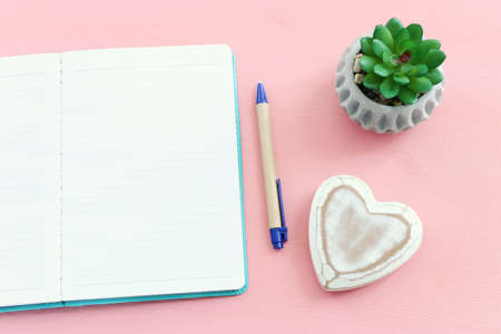 Empty open notebook and zen pebbles on pastel wooden background. copy space for text Standard-Bild