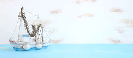 nautical concept with white decorative sail boat, seashells over wooden table and white background