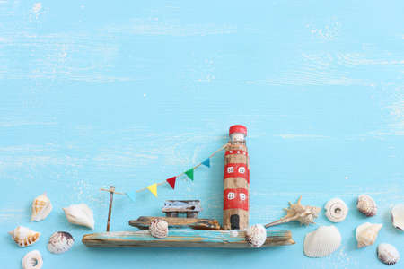 Top view of Nautical concept with sea life style objects as boat, driftwood beach houses, seashells and starfish over wooden background