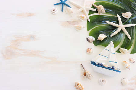 nautical concept with white decorative sail boat, seashells over wooden background