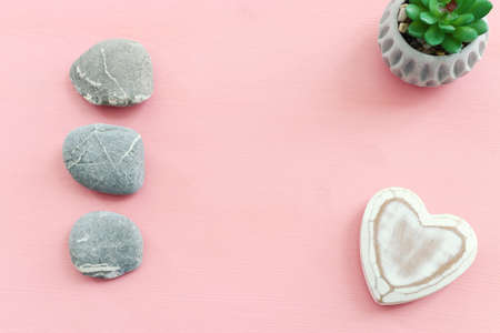 top view image of zen pebbles on pink background