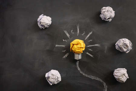 Education concept image. Creative idea and innovation. Crumpled paper as light bulb metaphor over blackboard Standard-Bild