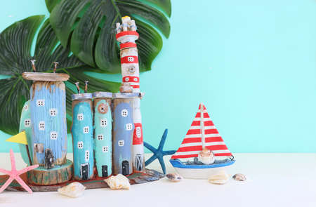 Nautical concept with sea life style objects as boat, driftwood beach houses, seashells and starfish over wooden table and blue background