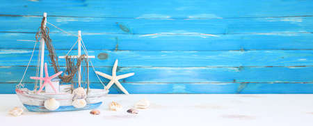 nautical concept with white decorative sail boat, seashells over wooden table and blue background Standard-Bild