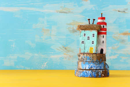 nautical concept with driftwood beach houses and lighthouse over wooden table Standard-Bild