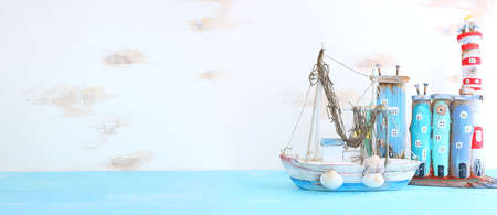 Nautical concept with sea life style objects as boat, driftwood beach houses and seashells over wooden background