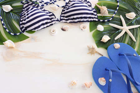 Top view of female swimsuit bikini, sea shells and starfish over white wooden background. Summer beach vacation concept Standard-Bild