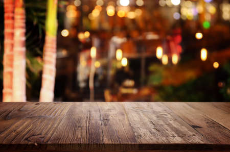 background Image of wooden table in front of abstract blurred restaurant lights Standard-Bild