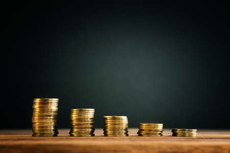 growing stack of coins on wooden table. financial success and management concept Standard-Bild