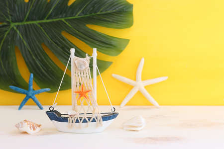 nautical concept with white decorative sail boat, seashells over wooden table and yellow background