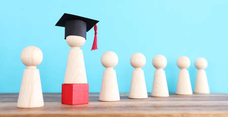 Image of education concept. Wooden people figure with graduation hat Stock Photo