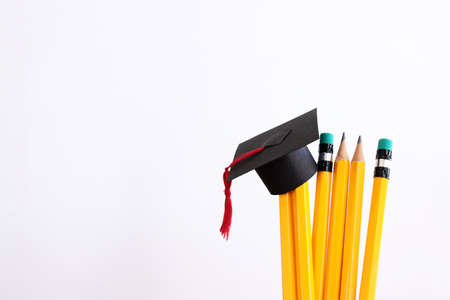 Image of education concept. Traditional graduation hat over pencils